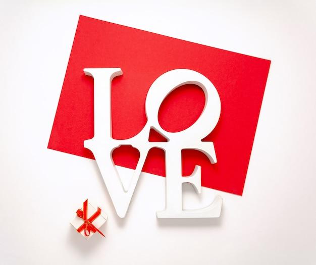 Assine amor vista superior dia dos namorados decorações plana leigos. palavra amor e caixa de presente pequena isolada no fundo vermelho branco