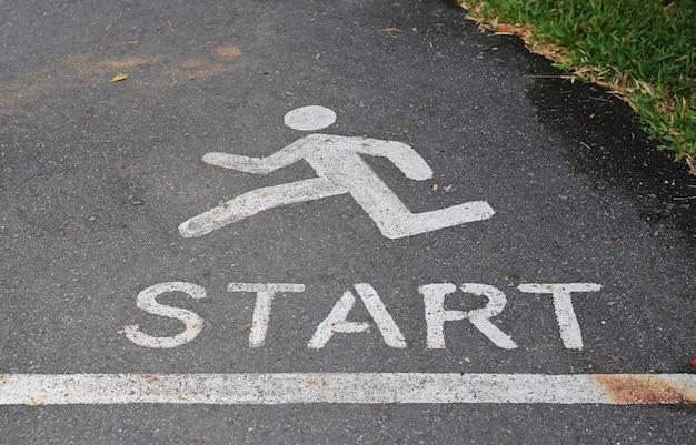 Assine o corredor e a palavra começam no ponto na rua do asfalto no parque.