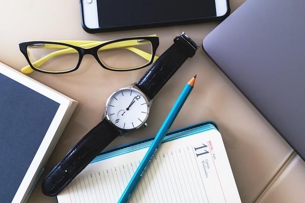Assista, óculos, telefone, laptop, caderno e lápis estão sobre a mesa.