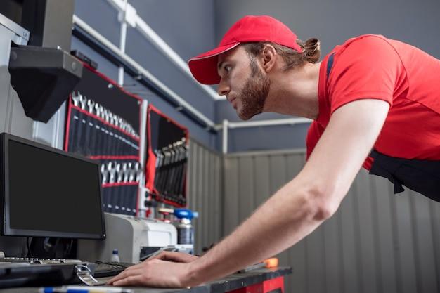 Assistência de informação. trabalhador jovem adulto atento e focado em uma oficina de boné vermelho e camiseta olhando interessado no computador