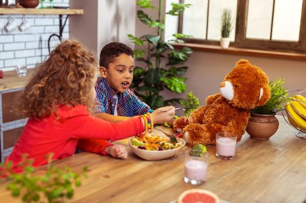Assistência médica. garoto internacional faminto sentado perto de um amigo e comendo comida saudável