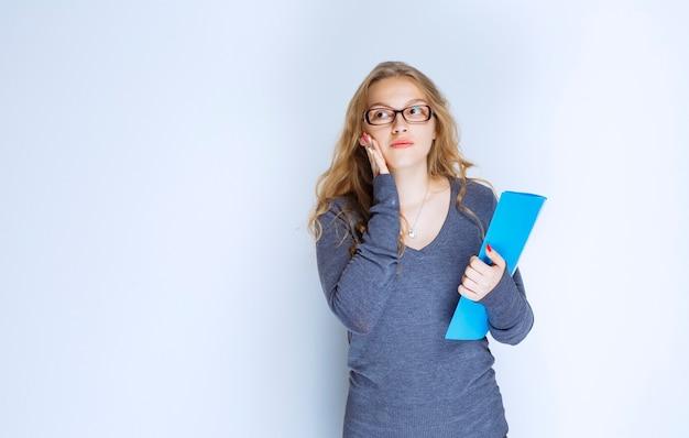 Assistente com óculos segurando uma pasta de relatório azul.