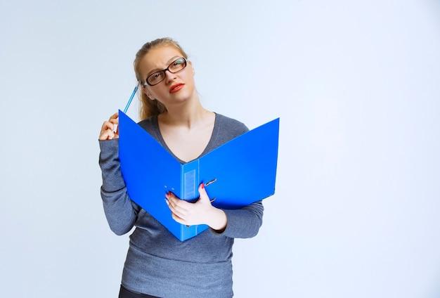 Assistente com óculos verificando a pasta azul e parece pensativo e confuso.