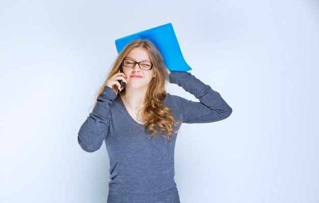 Assistente com uma pasta azul falando ao telefone e parece estressado porque algo está errado.