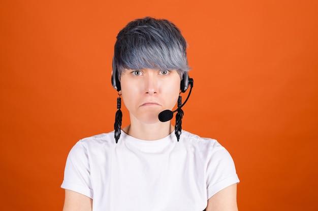 Assistente de call center com fones de ouvido na parede laranja e um rosto sério e infeliz olhando para a câmera
