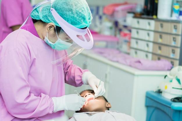 Assistente de dentista e dentista, verificação de dentes para crianças no saneamento.