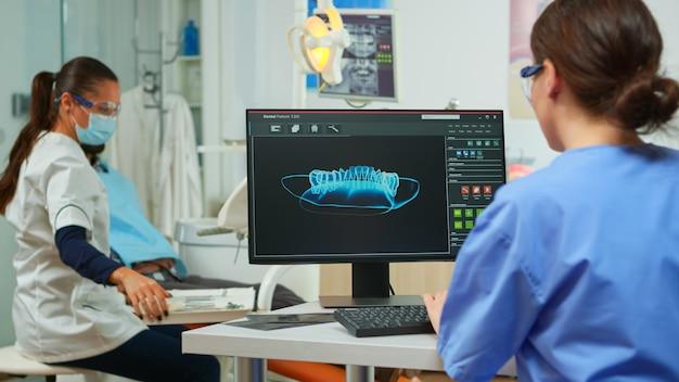 Assistente de dentista escrevendo parâmetros de impressão digital dental do paciente, enquanto médico especialista com máscara facial fala com homem com dor de dente sentado na cadeira de estomatologia preparando ferramentas