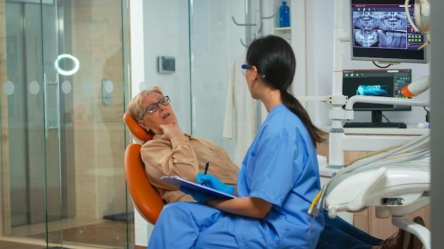 Assistente de dentista interrogando mulher sênior e fazendo anotações na área de transferência à espera do médico. paciente sênior em paing explicando problema dentário para enfermeira indicando problemas de dor de dente