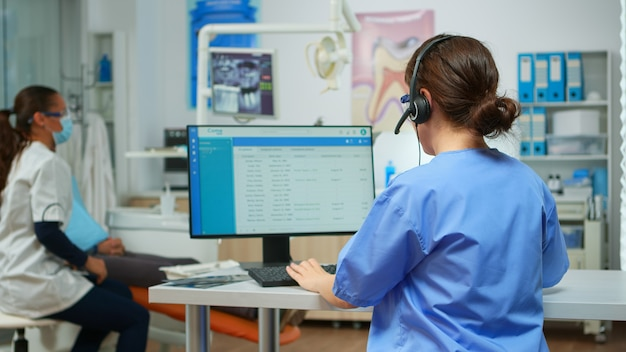 Assistente de dentista marcando consultas usando fone de ouvido sentado em frente no computador enquanto o médico está trabalhando com o paciente em segundo plano, examinando o problema dos dentes. enfermeira fazendo anotações em consultório de estomatologia