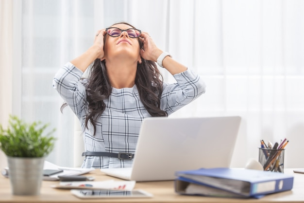 Assistente de escritório recostada na cadeira com a cabeça nas mãos devido a uma dor de cabeça no trabalho.