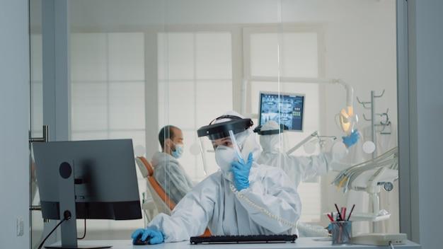 Assistente de estomatologia com macacão de epp usando computador