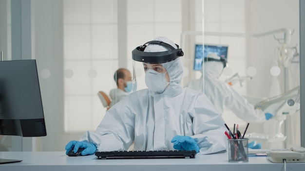 Assistente de estomatologia sentado na mesa usando o computador