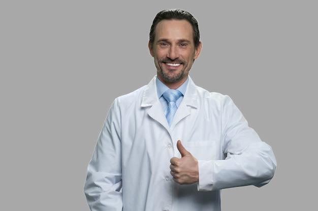 Assistente de laboratório bonito desistindo gesto de polegar. feliz cientista vestindo jaleco em fundo cinza. símbolo de sucesso.