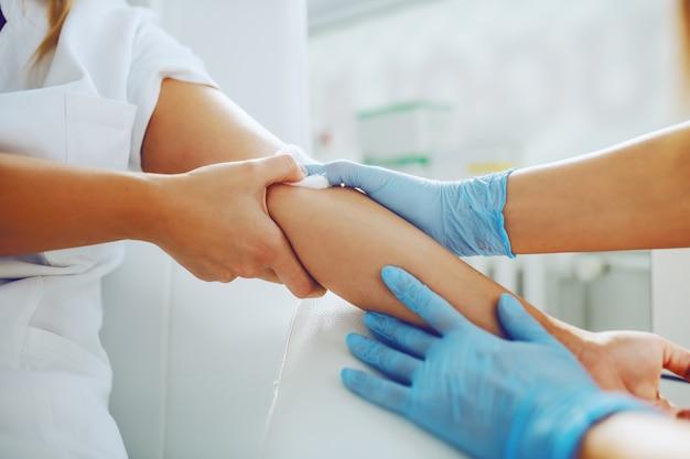 Assistente de laboratório colocando algodão absorvente no braço do paciente após a coleta da amostra de sangue.