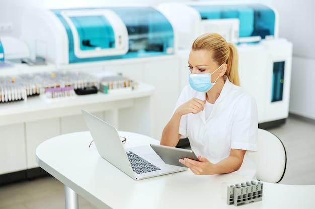 Assistente de laboratório experiente sentado no laboratório com máscara facial, segurando o tablet com resultados de teste e olhando para o laptop. pesquisa de cura para o conceito de vírus corona.