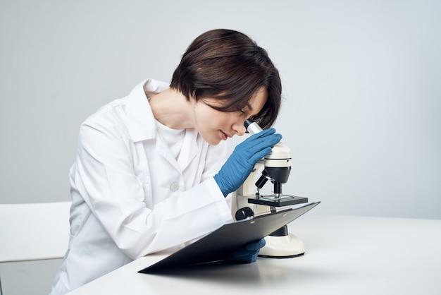 Assistente de laboratório feminino em biologia científica de jaleco branco