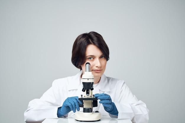 Assistente de laboratório feminino, estúdio de pesquisa científica de microscópio