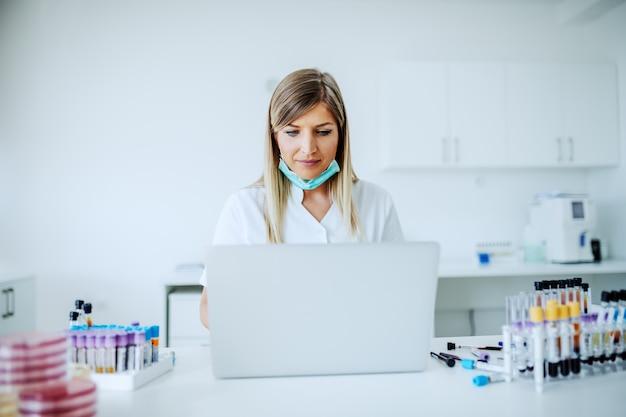 Assistente de laboratório loiro feminino caucasiano bonito sentado na mesa e usando o laptop para entrada de dados.