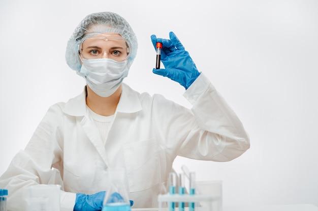 Assistente de laboratório médico em uma máscara sobre um fundo branco, segura um tubo de ensaio com o sangue de uma pessoa infectada.