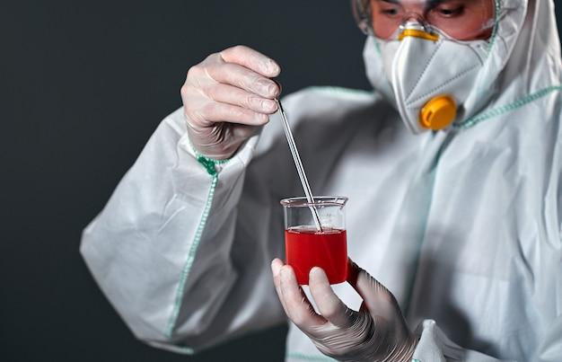 Assistente de laboratório médico masculino em um traje de proteção, um respirador e óculos detém uma pipeta e um frasco de vidro com sangue ou líquido vermelho isolado no preto.