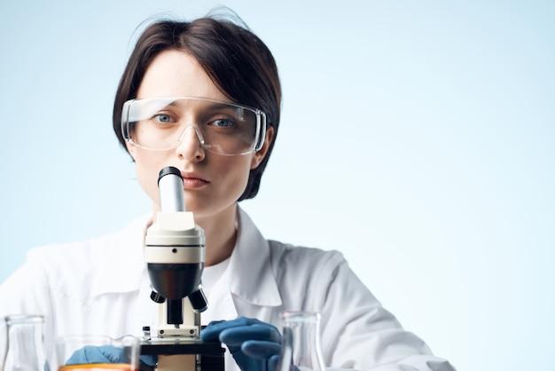 Assistente de laboratório sentado à mesa microscópio pesquisa biotecnologia luz de fundo