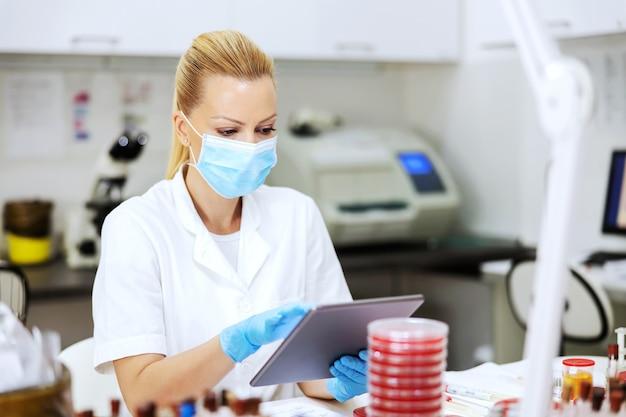 Assistente de laboratório sentado no laboratório e usando o tablet para inserir os resultados dos testes.