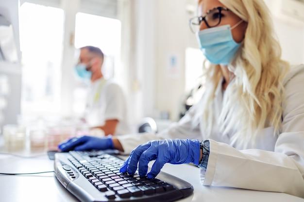 Assistente de laboratório usando laptop durante o vírus corona.