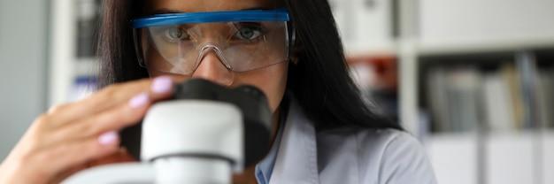 Assistente de laboratório usando microscópio