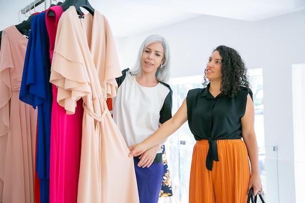 Assistente de loja ajudando o cliente a escolher o tecido. compradores tocando em um vestido novo pendurados na prateleira tiro médio. loja de moda ou conceito de varejo