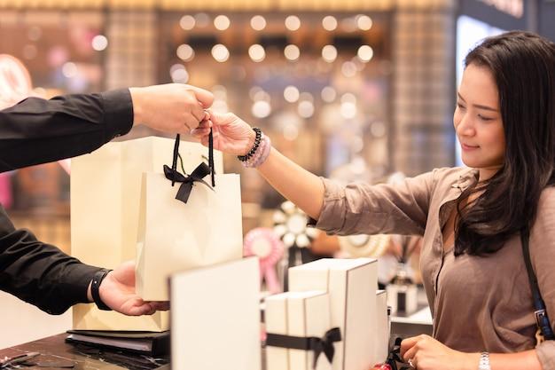 Assistente de loja, entregando a sacola de compras para o cliente do sexo feminino.