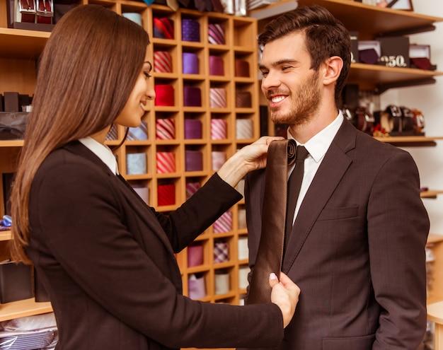 Assistente de loja feminino e oferecendo um empate ao empresário.
