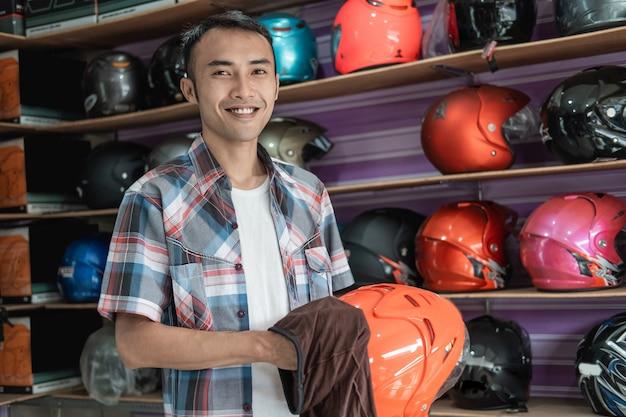 Assistente de loja masculino sorridente, limpando capacete com pano na loja de capacetes