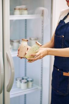 Assistente de loja oferecendo iogurte fresco com deliciosas frutas e bagas para o cliente