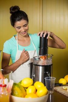 Assistente de loja preparando suco de frutas