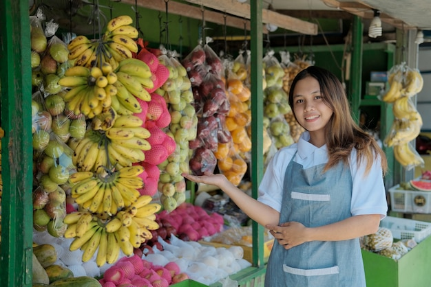 Assistente de loja sorridente ao lado de frutas orgânicas na barraca
