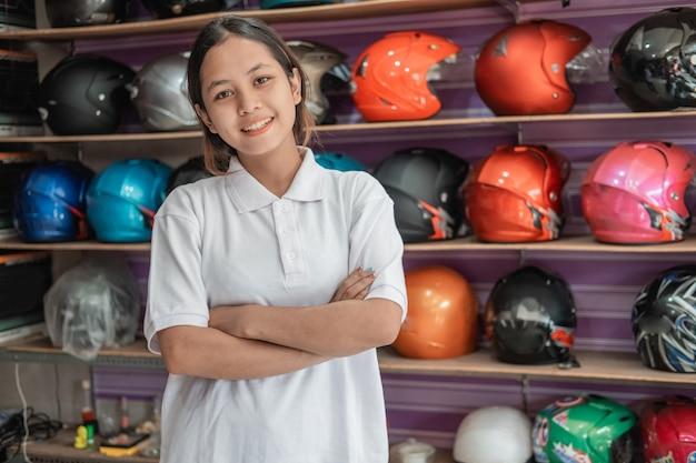 Assistente de loja sorrindo com as mãos cruzadas na loja de capacetes