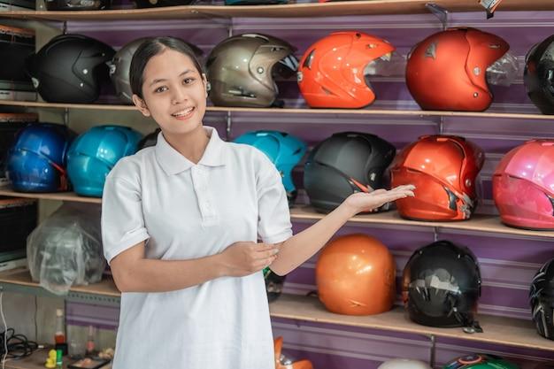 Assistente de loja sorrindo com gestos com as mãos para oferecer algo na loja de capacetes