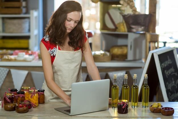 Assistente de loja usando laptop no balcão