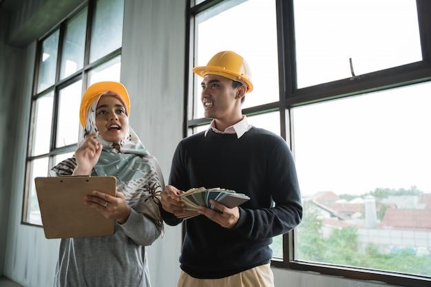 Assistente de mulher discute detalhes do projeto com o engenheiro-chefe