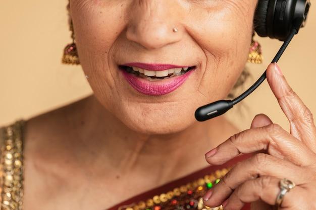 Assistente de operador indiano usando um fone de ouvido com microfone enquanto conversa com um cliente