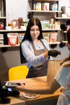 Assistente de vendas distribuindo a compra ao cliente