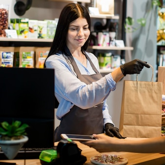 Assistente de vendas distribuindo sacola de compras para o cliente