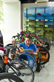 Assistente de vendas verificando bicicletas