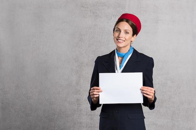 Assistente de vôo segurando placa branca