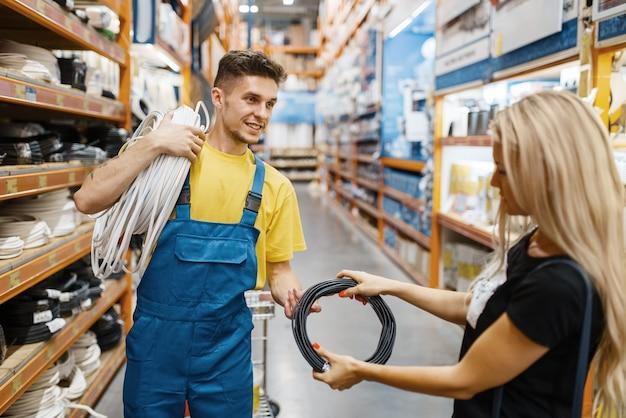 Assistente e cliente do sexo feminino com fios em loja de ferragens. vendedor de uniforme e mulher na loja de bricolage, fazendo compras em um prédio de supermercado