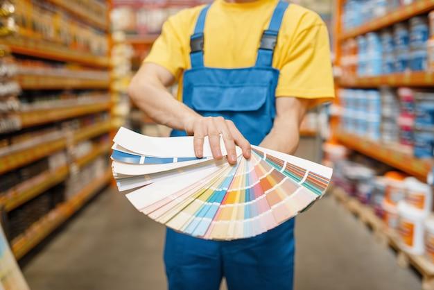 Assistente e cliente do sexo feminino com paleta de cores na loja de ferragens. vendedor de uniforme e mulher na loja de bricolage, fazendo compras em um prédio de supermercado