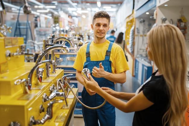 Assistente e cliente do sexo feminino escolhendo chuveiro na loja de ferragens. vendedor de uniforme e mulher na loja de bricolage, fazendo compras em um prédio de supermercado