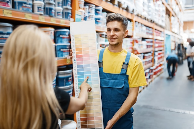 Assistente e cliente feminino em loja de ferragens. vendedor de uniforme e mulher na loja de bricolage, fazendo compras em um prédio de supermercado