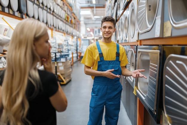 Assistente e compradora em loja de ferragens. vendedor de uniforme e mulher na loja de bricolage, fazendo compras em um prédio de supermercado