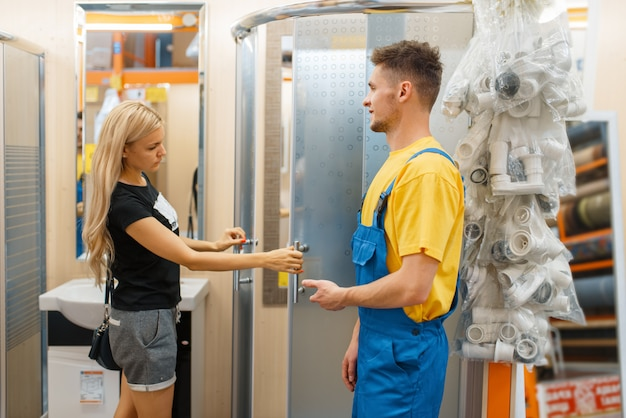 Assistente e consumidora em loja de ferragens. vendedor de uniforme e mulher na loja de bricolage, fazendo compras em um prédio de supermercado